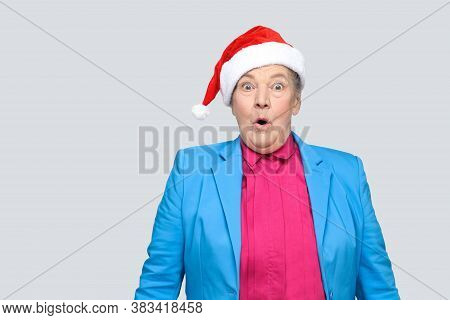 Surprised Grandmother In Colorful Casual Style With Blue Suit And Christmas Santa Red Cap Standing A
