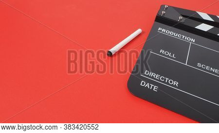 Black Clapperboard Or Movie Slate And Pen On Red Background.it Is Used In Video Production And Film