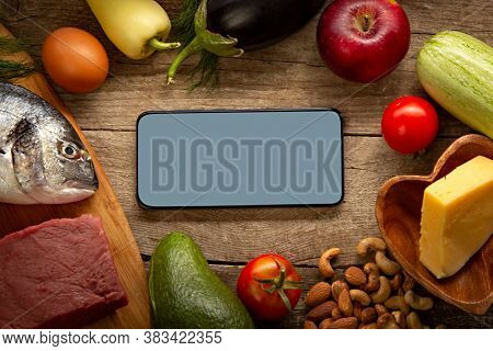 Keto diet inscription and food and smartphone. Healthy products. Diet concept low carbs. Vegetables, fish, meat, nuts, seeds, tomato, apple, cheese on a brown background. Top view.