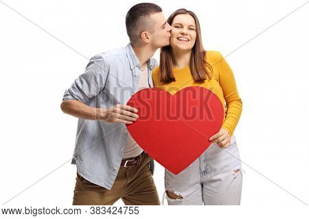 Young man kissing a female and holding a red heart isolated on white background