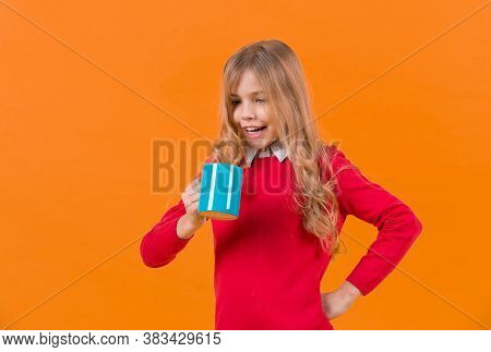 Child Smile With Blue Cup On Orange Background. Girl With Long Blond Hair In Red Sweater Hold Mug. T