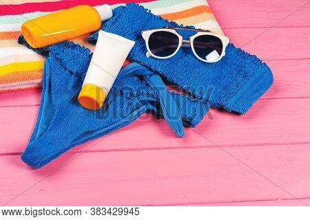 Blue Bikini With Sunblock Cream Bottle On Bright Pink Wooden Background