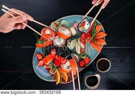 A Set Of Sushi On A Wooden Table In A Japanese Restaurant. Sushi And Sashimi On Sticks, Friends Eat
