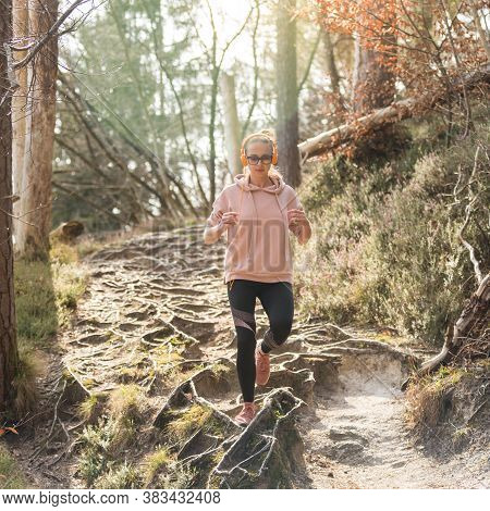 Active Sporty Woman Listening To The Music While Running In Autumn Fall Forest. Female Runner Traini