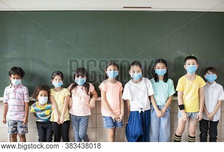 Group Of Diverse Young Students Wear Mask And Standing Together In Classroom
