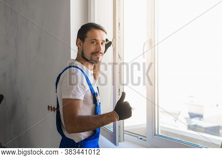 Male Repairer In Overalls Installs A Window And Showing Thumb