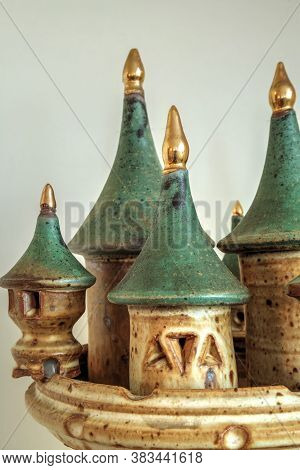 Pottery Castle With Turrets Tipped In Gold Against A White Background.