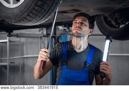 A Mechanic Inspects The Bottom Of A Car With A Flashlight