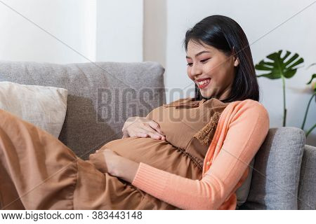 Asian Pregnant Woman Smile And Sitting On The Sofa With Feeling Happily And Relaxed. Ways To Create