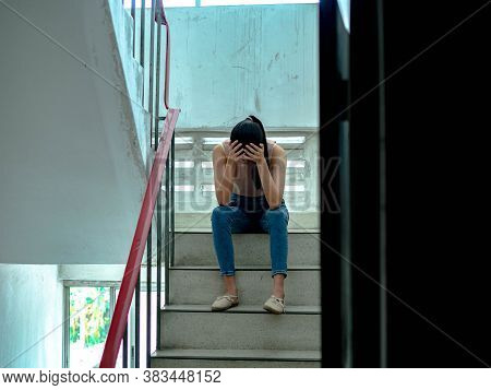 Unhappy Depressed Teenager With Face In Hands Sitting Stair, Thinking About Problem With Relationshi