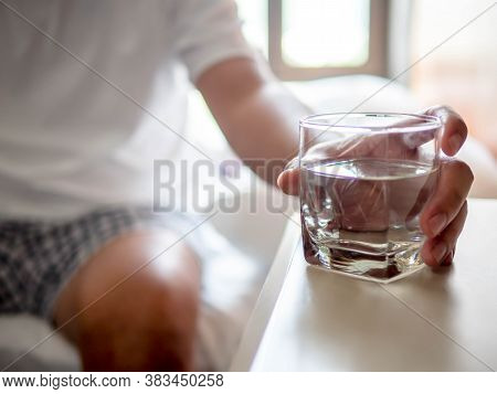 Hand Of Man Holding A Clear Glass Of Water For Drinking On Bed In The Morning