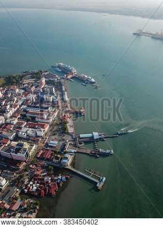 Georgetown, Penang/malaysia - Feb 29 2020: Aerial View Ferry Arrive Penang Jetty. Background Is Crui