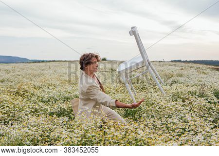Tall Handsome Man Standing In The Middle Of Camomile Flowers Field And Balancing With White Chair On