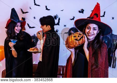 Young Asian Woman In Costume Celebrating Halloween Holding A Carved Pumpkin. Celebration Of Group Yo