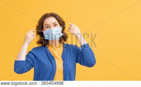 Young woman wearing facemask during coronavirus and flu outbreak. Virus and illness protection, home quarantine. COVID-2019. Taking on or taking off masks. Person on yellow color background.