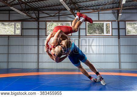 Greco-roman Wrestling Training, Grappling. Two Greco-roman  Wrestlers In Red And Blue Uniform Wrestl
