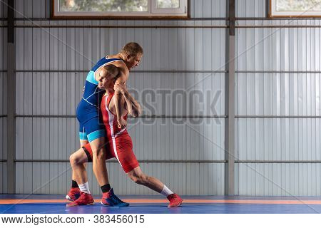 Two Greco-roman  Wrestlers In Red And Blue Uniform Wrestling  On Background On A Blue Wrestling Carp