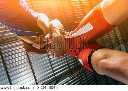 Close-up Two Wrestlers Of Grappling And Greco-roman Wrestler In A Blue And Red Tights Makes Armbar .