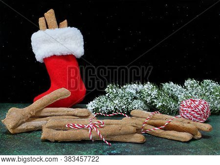 Dog Cookies Shaped Like Sticks Being Wrapped For Christmas And In A Stocking For The Holiday. Black