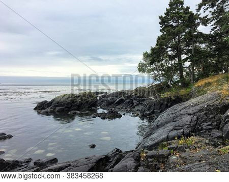 Beautiful Photo Of A Picturesque Rocky Shoreline Surrounded By Evergreen Forest And A Vast Ocean, Al