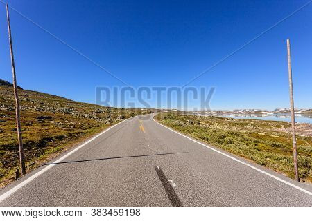 Empty Road Crossing Hardangervidda Plateau In Summer Time, Norway Landscape. National Tourist Hardan