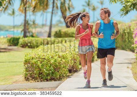 Happy runners couple running together talking training outside on city sidewalk. Woman and man jogging healthy cardio workout lifestyle.