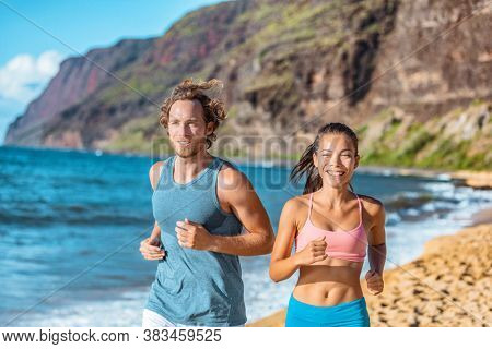 Happy healthy active athletes training together on beach. Smiling Asian woman runner running with man friend outdoors in summer.
