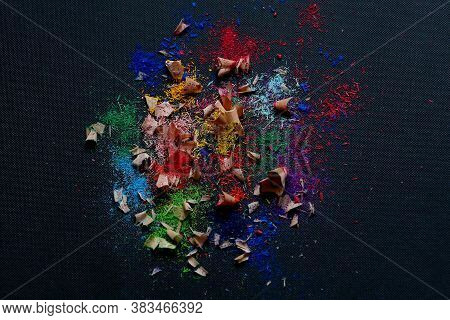 Colorful Pencil's Shavings Are On The Black Fabric Texture Background Close Up Taken With Copy Space
