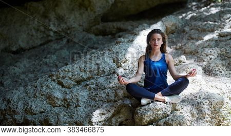 Female In Lotus Position. Outdoors Training. Meditation Or Yoga Time And Pilates Idea. Nature And Ma