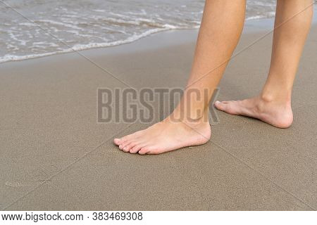 Close-up Of Childs Legs Walking On Sand Coast And Sea Water. Young Girl Legs On Baltic Sea Beach. Te