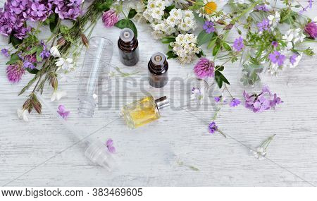 Essential Oil Bottles And Freshness  Flowers  On  A White Table