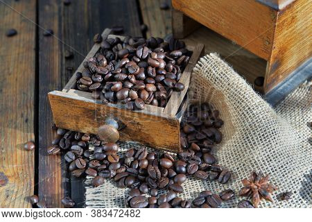 Drawer Of A Coffee Grinder Filled With Grain On Rustic Wooden Background