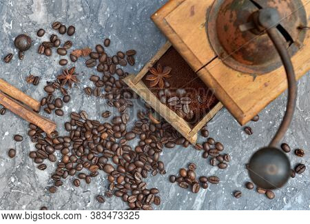 Top View On Old Coffee Grinder Full Of Coffee And Beans With Spices On Grey Marble Bacground