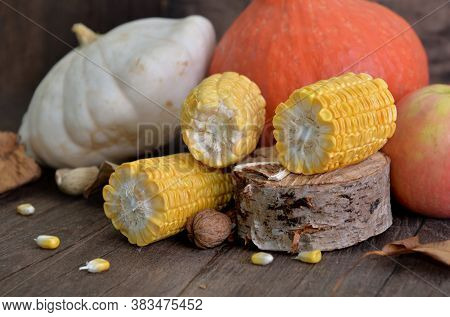 Fresh Corn Cut Into Pieces In Front Of Various And Colorful Autumnal Vegetables And Fruits On Wooden