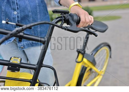 Bicyclist Holds Yellow Bicycle Behind Wheel. Bicycle Rental And Rental Concept