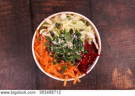 Delicious Mixed Salad With Seeds, Red Beets, Carrots And Cabbage On The Wooden Table, Top View