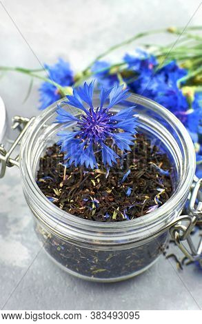 Blend Of Black Tea, Cornflowers Petals And Thyme In Glass Jar With Fresh Blue Cornflowers