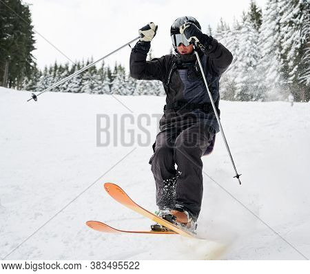 Man Skier In Black Ski Suit And Goggles Skiing Downhill Trough Deep Powder Snow. Young Man Freerider