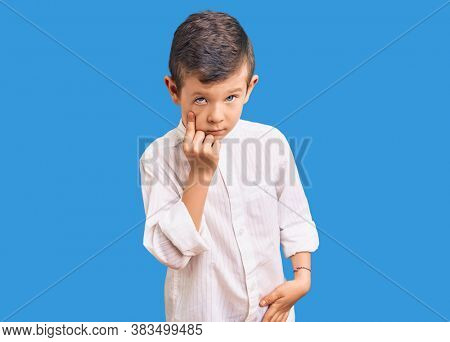Cute blond kid wearing elegant shirt pointing to the eye watching you gesture, suspicious expression