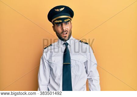 Handsome hispanic man wearing airplane pilot uniform in shock face, looking skeptical and sarcastic, surprised with open mouth