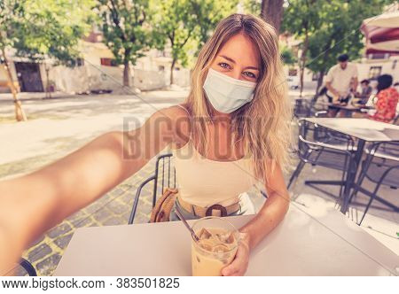 Woman Wearing Protective Face Mask On Mobile Video Calling Friends In Coffee Shop In The New Normal