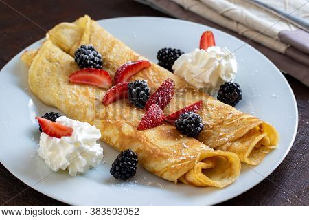 Close Up Of Thin Crepes Dessert With Whipped Cream And Red Fruits.