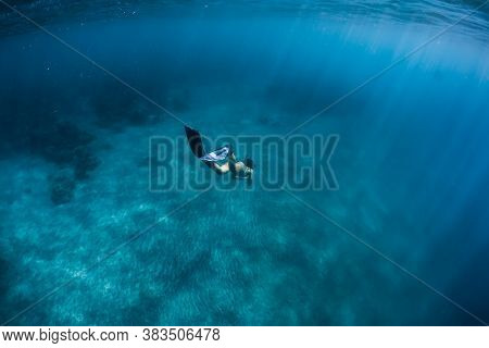 Woman Freediver Glides Over Sandy Bottom With Fins. Freediving In Blue Ocean