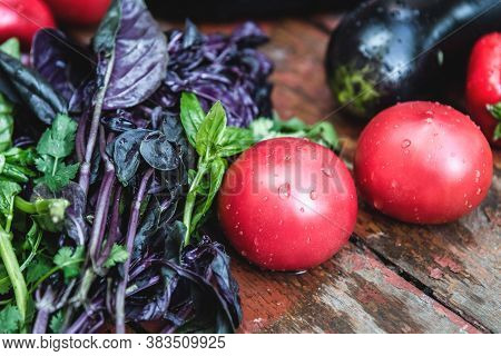 Farm Tomatoes, Eggplants And Greens Lie On A Wooden Surface. Concept Of Biological, Bio Products, Bi