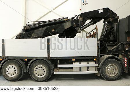 Truck With A Crane In The Back. Transport - A Truck With A Crane In The Back At The Warehouse.