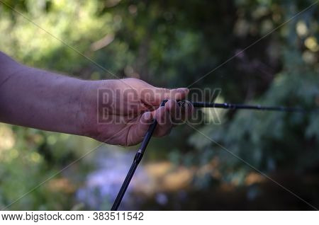 The Male Hands Collect The Plug-in Fishing Rod. Caucasian Man Assembles Casting Rod Outdoors. Sports