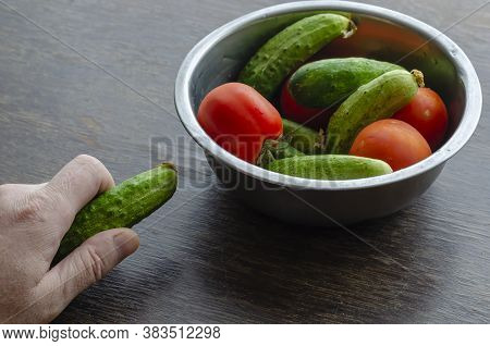 Male Hand Is Holding Fresh Cucumber. Metal Bowl With Tomatoes And Cucumbers In The Background. Middl