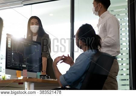 Three asian business person discuss their work in morning after office reopen due to coronavirus COVID-19 pandemic. They wear protective face mask to prevent infection. New normal office life concept.