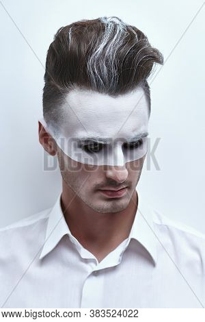 Fashion art portrait of a handsome man with white paint on his face and hair posing in white shirt on a white background. Male beauty, fashion. Hairstyle and cosmetics.