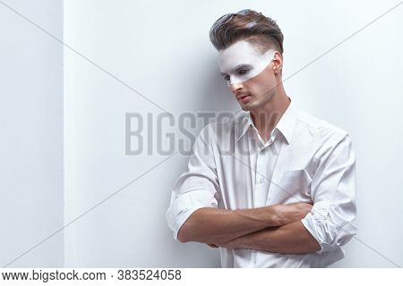 Art fashion portrait of a handsome man with white paint on his face and hair posing in white shirt by the white wall. Male beauty, fashion. Hairstyle and cosmetics. Copy space.